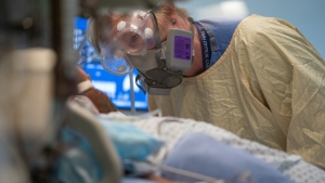 Registered nurse Linda Wright speaks to a patient in the COVID-19 Intensive Care Unit at Surrey Memorial Hospital in Surrey, B.C., Friday, June 4, 2021. THE CANADIAN PRESS/Jonathan Hayward