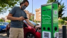 A man charges his electric car at an electrical charging point in Rivas Vaciamadrid, Spain, on June 15, 2021. (Manu Fernandez / AP)