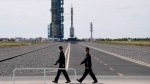 Officials walk across the tarmac ahead of liftoff at the Jiuquan Satellite Launch Center in Jiuquan in northwestern China, Thursday, June 17, 2021. (AP Photo/Ng Han Guan)