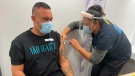 In this photo released by New Zealand Ministry of Health, Aaron Te Moananua, left, receives a dose of the Pfizer COVID-19 vaccine in Auckland, New Zealand, Tuesday, March 9, 2021. (New Zealand Ministry of Health via AP)