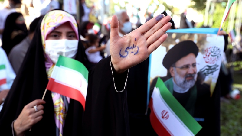"""A supporter of presidential candidate Ebrahim Raisi shows her hand with writing in Persian that reads """"Raisi"""", during a rally in Tehran, Iran, Wednesday, June 16, 2021. (AP Photo/Ebrahim Noroozi)"""