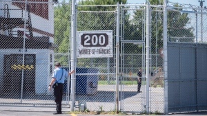A guard stands outside the gates of an immigrant holding centre in Laval, Que., Monday, August 15, 2016. (THE CANADIAN PRESS/Graham Hughes)