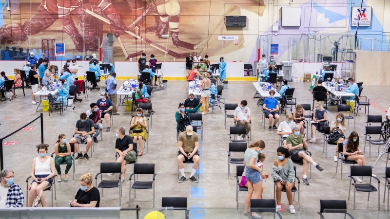 People are shown at the Bill Durnan Arena COVID-19 vaccination site in Montreal, Saturday, May 22, 2021. THE CANADIAN PRESS/Graham Hughes