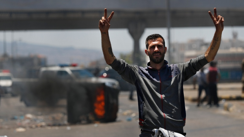 A protester flashes victory signs, as he stands in front of burned garbage containers that block a main highway, during a protest against the increase in prices of consumer goods and the crash of the local currency, in Beirut, Lebanon, Thursday, June 17, 2021. Shops, government offices, businesses and banks shut their doors Thursday in response to a call for a general strike by Lebanon's main labor union. (AP Photo/Hussein Malla)