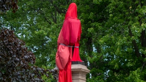 The statue of former Canadian Prime Minister Sir John A Macdonald is covered by a red sheet in Kingston, Ontario on Friday June 11, 2021. Local indigenous groups want the statue removed but the City of Kingston has not decided what to do with the statue and is leaving it up in the mean time. THE CANADIAN PRESS/Lars Hagberg