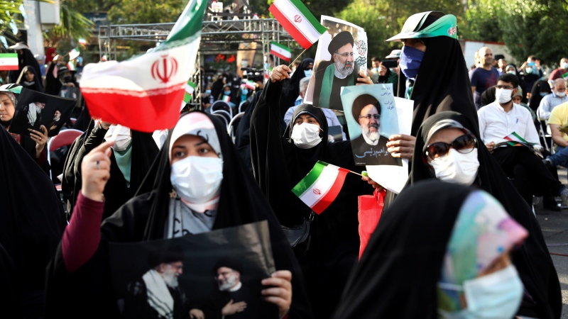 Supporters of presidential candidate Ebrahim Raisi hold signs during a rally in Tehran, Iran, Wednesday, June 16, 2021. (AP Photo/Ebrahim Noroozi)