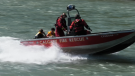 The Calgary Fire Department aquatics rescue team brings two rafters back to shore after their raft capsized Thursday morning. A second trip was made to retrieve the third member of the rafting group.
