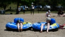 Matthew Nadon, 10, and his brother James Gordon, 13, sit in their inflatable tubes after floating in the Rideau River at Mooney's Bay Beach in Ottawa, on Saturday, June 12, 2021. (Justin Tang/THE CANADIAN PRESS)