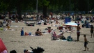 People enjoy the warm weather at Mooney's Bay Beach in Ottawa, on Saturday, June 12, 2021. (Justin Tang/THE CANADIAN PRESS)
