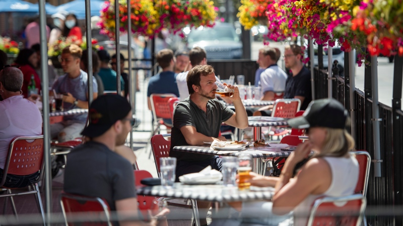 A patron drinks a beverage at a patio in the ByWard Market in Ottawa, as patios open in Ontario's first phase of re-opening amidst the third wave of the COVID-19 pandemic, on Saturday, June 12, 2021. (Justin Tang/THE CANADIAN PRESS)