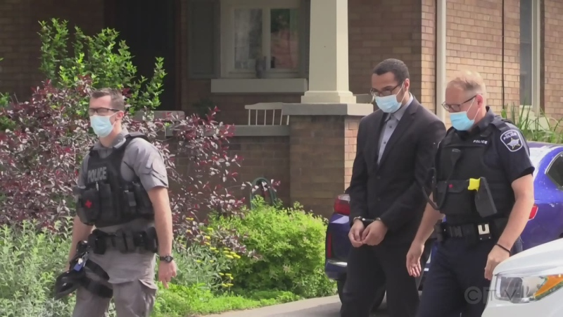 Dyrrin Daley is escorted by police to the William Street residence in Barrie, Ont. on Fri. June 11, 2021, where two men were killed. (Mike Arsalides/CTV News)