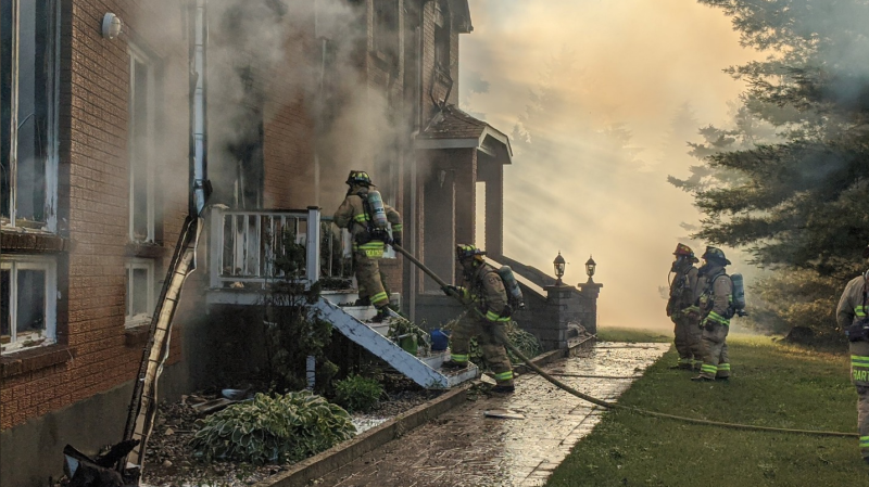 Ottawa firefighters battling a fire at a home along the Rideau River. (Photo courtesy: Twitter/OFSFirePhoto)