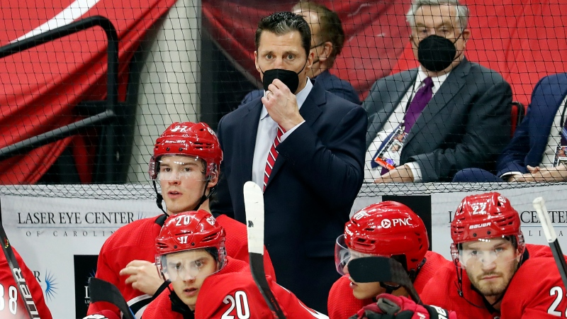 Carolina Hurricanes coach Rod Brind 'Amour, center, watches play from behind the bench during the third period of the team's NHL hockey game against the Detroit Red Wings in Raleigh, N.C., Thursday, April 29, 2021. (AP Photo/Karl B DeBlaker)