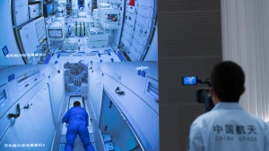 In this photo released by Xinhua News Agency, a worker monitors screens showing the interior of the Tianhe space station module after Chinese astronauts docked and enter it are displayed on large screens at the Beijing Aerospace Control Center in Beijing, on Thursday, June 17, 2021. (Jin Liwang/Xinhua via AP)