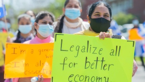 People take part in a rally calling on the federal government to expand the permanent status program to include all refugees, international students, undocumented migrants and temporary foreign workers near Prime Minister Justin Trudeau's constituency office in Montreal, Sunday, May 16, 2021. (THE CANADIAN PRESS/Graham Hughes)
