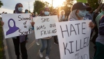 Young women walk with signs in London Ont. on Friday, June 11, 2021 during a Multi-Faith March to End Hatred after four members of a Muslim family were killed on Sunday in what police called a hate crime. THE CANADIAN PRESS/Geoff Robins