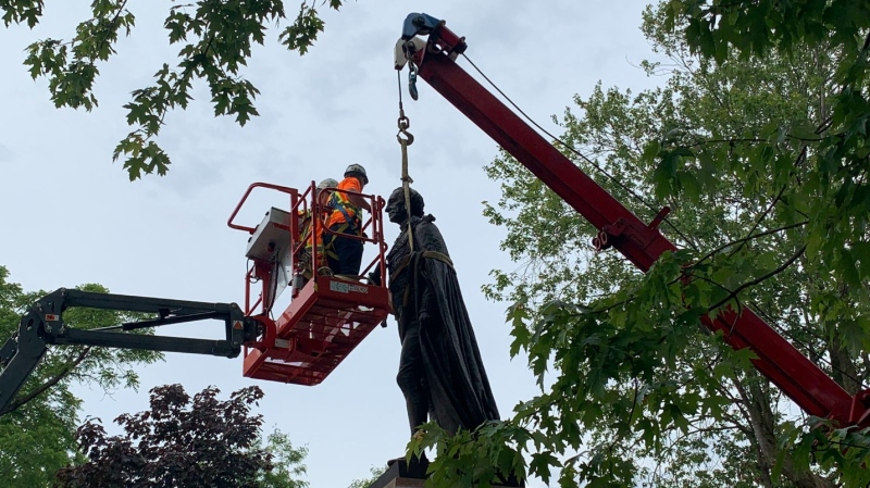 Crews attach straps to remove the statue of Sir John A. Macdonald from a Kingston, Ont. park Friday morning. (Kimberley Johnson/CTV News)