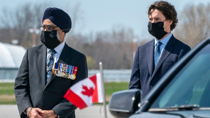 Prime Minister Justin Trudeau and Defence Minister Harjit Sajjan stand by a hearse during the repatriation ceremony for the six Canadian Armed Forces members killed in a helicopter crash off of Greece during Operation Reassurance, at CFB Trenton, Ont. on Wednesday, May 6, 2020. THE CANADIAN PRESS/Frank Gunn