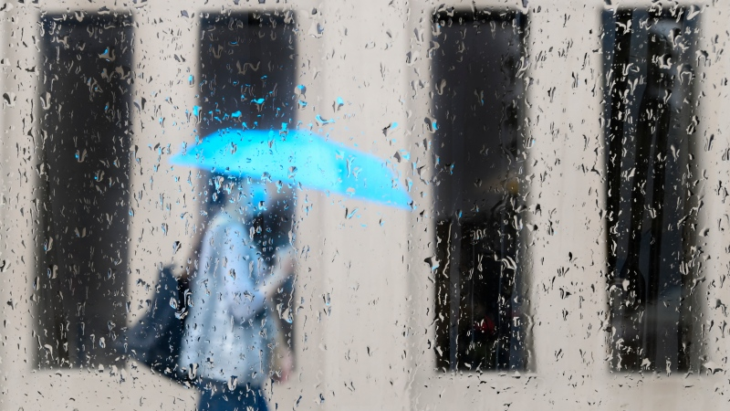 A pedestrian walks alongside businesses on a rainy day while wearing a protective mask during the COVID-19 pandemic in Toronto on Friday, June 18, 2021. THE CANADIAN PRESS/Nathan Denette