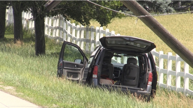 A minivan is seen abandoned north of London, Ont. after it struck a hydro pole Friday, June 18, 2021. (Daryl Newcombe / CTV News)