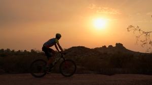 A cyclist bikes past the setting sun at Papago Park during a heatwave where temperatures hit 115-degrees Tuesday, June 15, 2021, in Phoenix. (AP Photo/Ross D. Franklin)