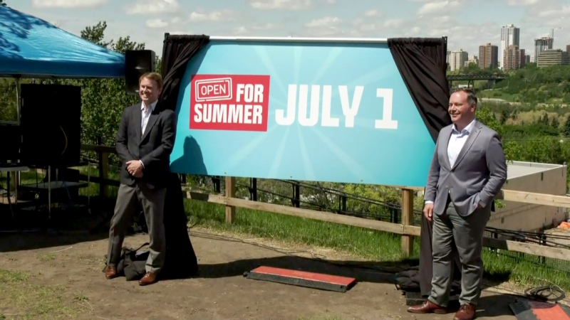 Premier Jason Kenney, right, and Health Minister Tyler Shandro pose for photos after announcing the province will move to Stage 3 of reopening on July 1, meaning all health measures will be lifted.