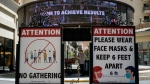 Signs with social distancing guidelines and face mask requirements are posted at an outdoor mall amid the COVID-19 pandemic in Los Angeles Friday, June 11, 2021. (AP Photo/Damian Dovarganes)