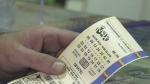 A man holds a Lotto Max ticket in his hand in Barrie, Ont. on Fri. June 18, 2021 (Katelyn Wilson/CTV News)