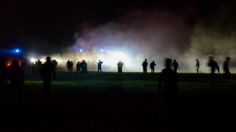 Youths stand in a field during clashes as police tried to break up an unauthorized rave party near Redon, Brittany, Friday June 18, 2021. Police repeatedly fired tear gas and charged clusters of violent partiers who hurled metal balls, gasoline bombs and other projectiles at security forces, according to images of the clashes shared online and the top government official in the region. Local authorities estimated about 1,500 people took part despite a local ordinance banning the event. (AP Photo)
