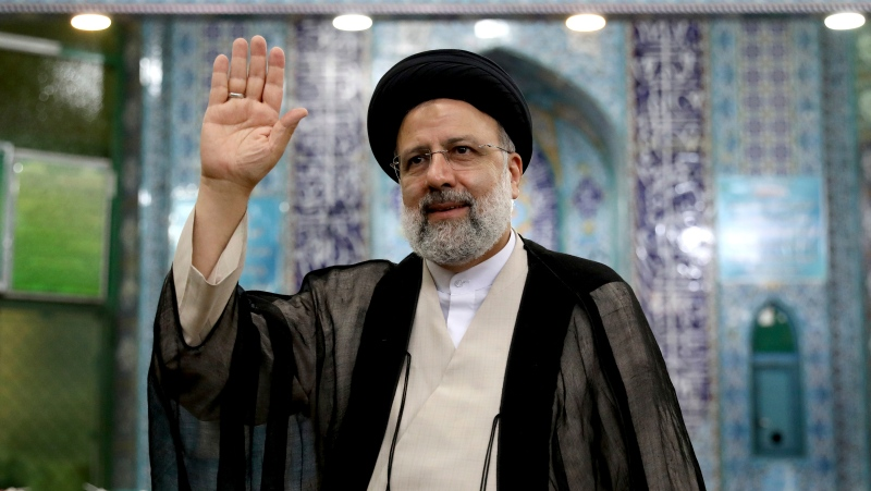Ebrahim Raisi waves to the media after casting his vote at a polling station in Tehran, Iran Friday, June 18, 2021. Iran began voting Friday in a presidential election tipped in the favor of a hard-line protege of Supreme Leader Ayatollah Ali Khamenei, fueling public apathy and sparking calls for a boycott in the Islamic Republic. (AP Photo/Ebrahim Noroozi)