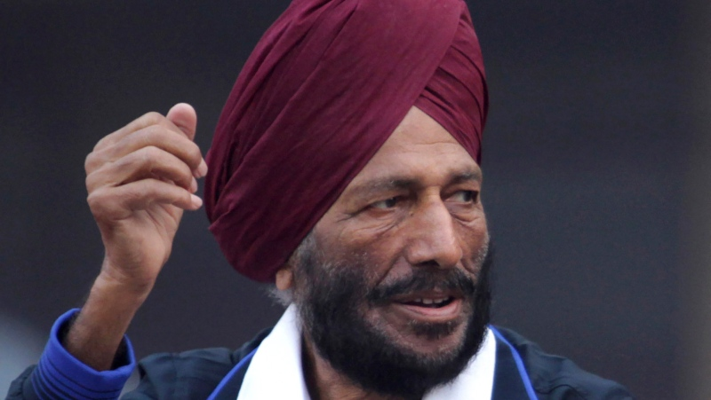 In this Dec. 15, 2013, file photo, former Indian athlete Milkha Singh waves to the participants during the Delhi Half Marathon in New Delhi, India. Milkha Singh, one of India's first sport superstars and ace sprinter who overcame fought a childhood tragedy and became the country's most celebrated athlete, has died. He was 91.(AP Photo/Tsering Topgyal, File)