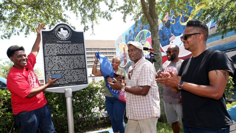 Sam Collins III, left, and others celebrate at the Juneteenth historical marker in Galveston after President Joe Biden signed the Juneteenth National Independence Day Act into law on Thursday, June 17, 2021. (Jennifer Reynolds/The Galveston County Daily News via AP)