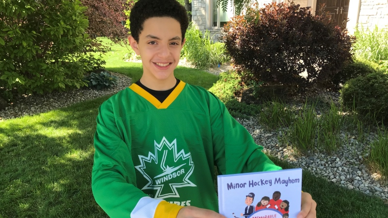 """Ziyad Emara, 15, holds up a copy of his book """"Minor Hockey Mayhem"""", written during the pandemic because he misses his sport. (Michelle Maluske/CTV Windsor)"""