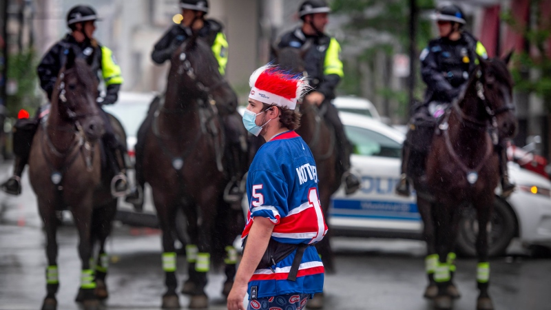 A Montreal Canadiens fan passes by mounted police outside the Bell Centre prior to Game 3 of the NHL Stanley Cup semifinal against the Vegas Golden Knights in Montreal, Friday, June 18, 2021. THE CANADIAN PRESS/Peter McCabe