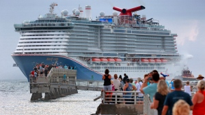 Fans line up at Jetty Park to see the Carnival Cruise Line ship Mardi Gras arrive at Port Canaveral, Fla., early Friday morning, June 4, 2021.  (Joe Burbank/Orlando Sentinel via AP)