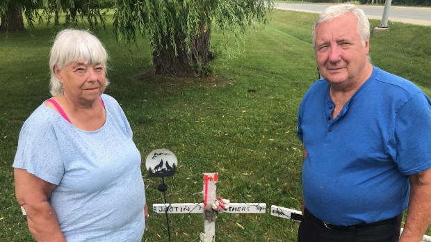Judy and Glen Struthers stand before the memorial cross to their Grandson, Justin Struthers. It's one if 18 infront of the provincial government property leading to the Elgin-Middlesex Detention Centre, June 19, 2021 (Sean Irvine/CTV news)