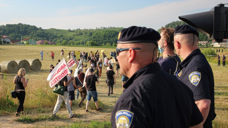 Croatian police officers stand as people walk with banners during a protest against the violent pushbacks of migrants, allegedly conducted by Croatian police, near the border crossing between Croatia and Bosnia Herzegovina in Maljevac, Croatia, Saturday, June 19, 2021. (AP Photo/Edo Zulic)