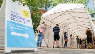 People wait in line to receive a COVID-19 vaccine in Montreal, Saturday, June 19, 2021. THE CANADIAN PRESS/Graham Hughes