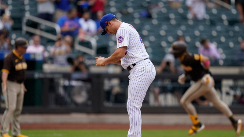 New York Mets relief pitcher Jacob Barnes, center, reacts after giving up a grand slam to San Diego Padres' Fernando Tatis Jr., right, during the seventh inning of a baseball game at Citi Field, Sunday, June 13, 2021, in New York. (AP Photo/Seth Wenig)