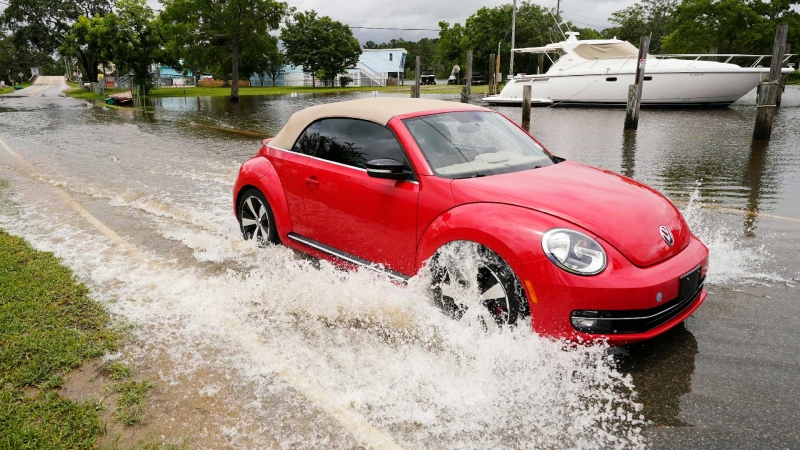 A passenger car drives through a road flooded by the Tchoutacabouffa River along Cedar Lake Road in Biloxi, Miss., Saturday, June 19, 2021, as water from Tropical Storm Claudette begins to recede. The storm brought much evening and early morning rain and flooded various communities along the Mississippi Gulf Coast. (AP / Rogelio V. Solis)