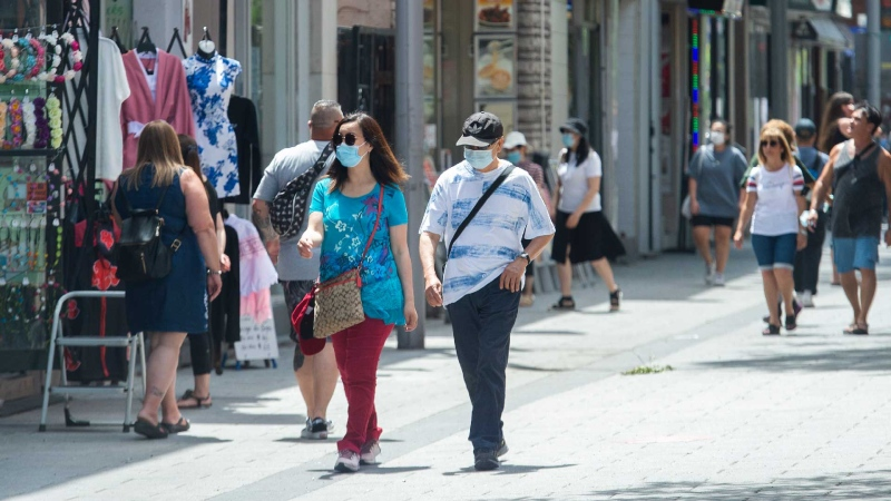 People wear face masks to prevent the spread of COVID-19 as they walk through Chinatown in Montreal, Saturday, June 19, 2021. The city of Montreal unveiled an action plan Friday to protect the historic sector. THE CANADIAN PRESS/Graham Hughes