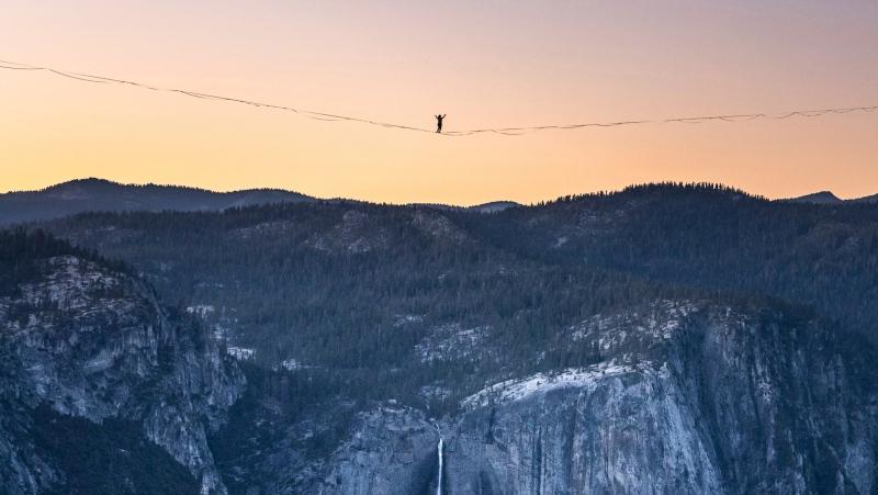 In this Saturday, June 12, 2021, photo provided by Scott Oller Films, highliner Daniel Monterrubio walks the 2,800-foot-long line off Taft Point above Yosemite Valley in Yosemite, Calif. (Scott Oller/Scott Oller Films via AP)