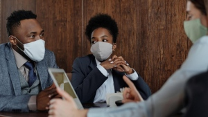 Group of people wearing masks during a business meeting. (Pexels, August de Richelieu)