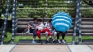 Kids take shelter from the sunlight on a covered bench as one also uses an umbrella at Queen Elizabeth Park, in Vancouver, B.C., in this July 16, 2018 file photo. THE CANADIAN PRESS/Darryl Dyck