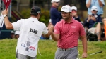 Jon Rahm, of Spain, celebrates with his caddy after making his birdie putt on the 18th green during the final round of the U.S. Open Golf Championship, Sunday, June 20, 2021, at Torrey Pines Golf Course in San Diego. (AP Photo/Marcio Jose Sanchez)