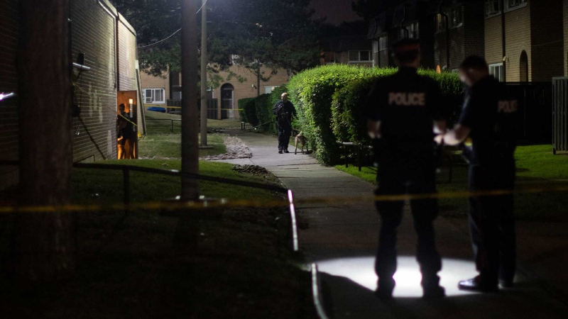 Police officers search at the scene of a shooting in Etobicoke in northwest Toronto on Saturday, June 19, 2021. THE CANADIAN PRESS/Chris Young
