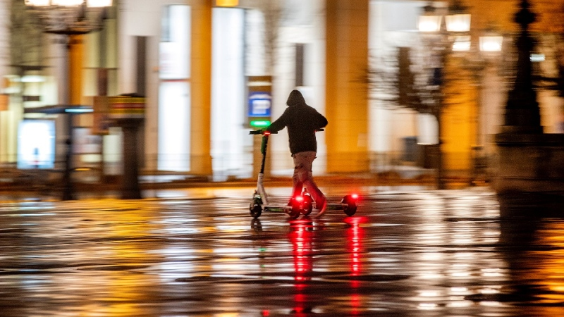 A man collects e-scooters for charging in the city centre in Frankfurt, Germany, on Feb. 6, 2021. (Michael Probst / AP)