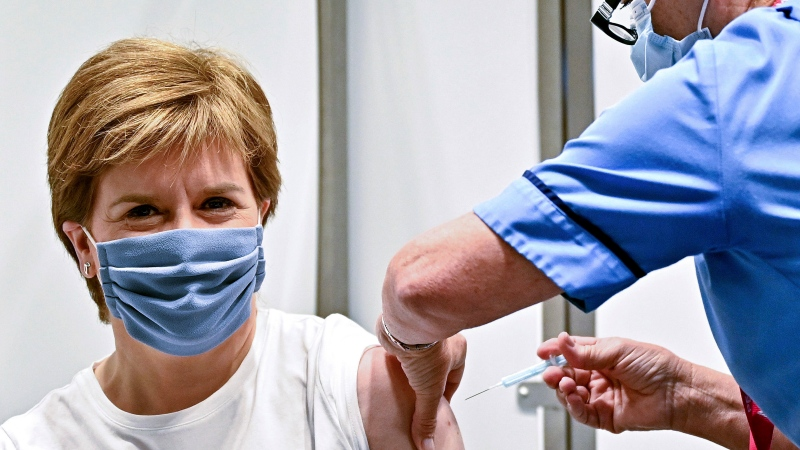 First Minister of Scotland Nicola Sturgeon receives her second dose of the AstraZeneca COVID-19 vaccine, administered by staff nurse Susan Inglis, at the NHS Louisa Jordan vaccine centre in Glasgow, Scotland, Monday June 21, 2021. (Jeff J Mitchell/Pool via AP)