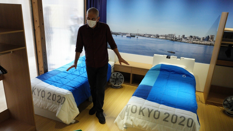 A journalist looks at cardboard beds for the Tokyo 2020 Olympic and Paralympic Villages, which are shown in a display room the Village Plaza on June 20, 2021, in Tokyo. (AP Photo/Eugene Hoshiko)