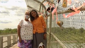 Muskoday First Nation Chief Ava Bear (left) and Ronalda Vandale (right) pose after hanging two pairs of children's moccasins on the Muskoday bridge on June 21, 2021. (Jayda Taylor/CTV Prince Albert)